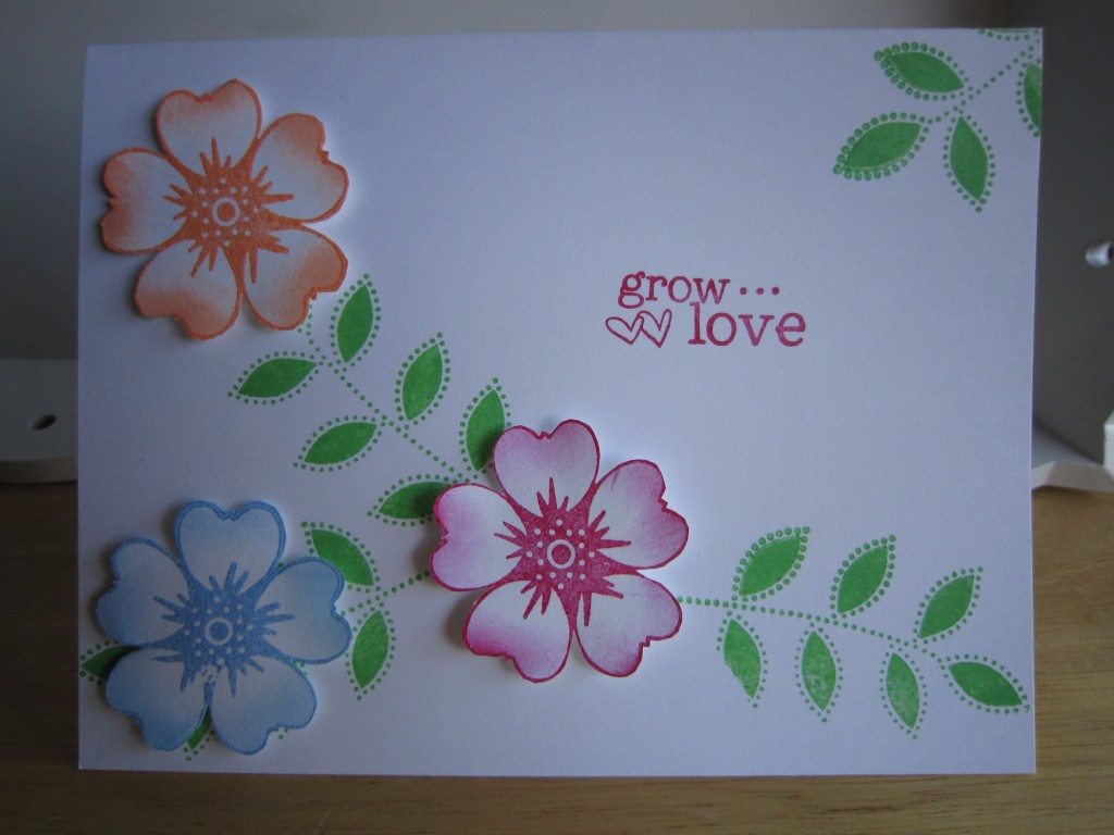 "A white card with three colored flowers and the message, ""grow love"""